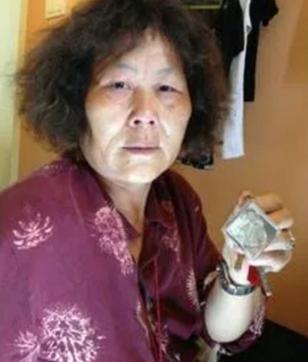 Một phụ nữ lớn tuổi bên bức ảnh người con trai đã mất - Ảnh: Internet