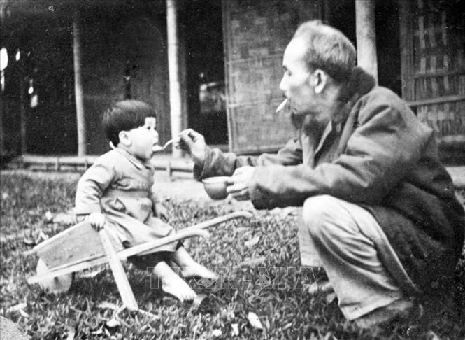 Bác Hồ bón cơm cho một cháu bé khi đến thăm trại nhi đồng ở chiến khu Việt Bắc (1950). Ảnh: Tư liệu TTXVN