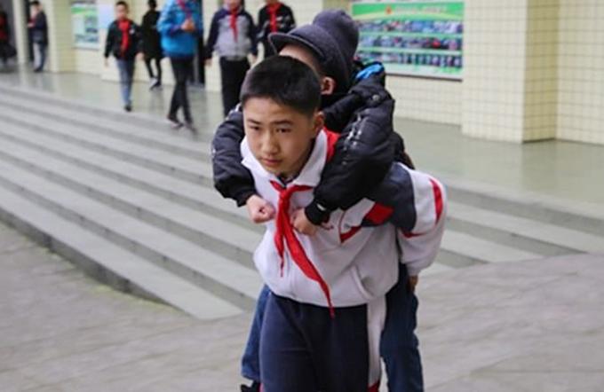 Một cậu bé ở Trung Quốc cõng bạn tới trường mỗi ngày