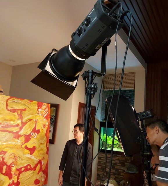 Photographer Minh Khánh (trái) đang chụp tranh họa sĩ Đinh Phong lại xưởng làm việc, sáng 15.3.2021 tại Sài Gòn.